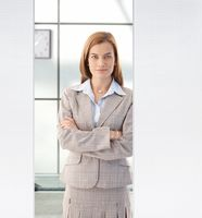 Pretty businesswoman standing in office smiling