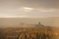 City autumn landscape of the park part of the city in the pre-smoke haze in warm tones. Catholic church against the background of high-rise buildings