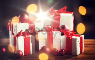 gift boxes and red christmas balls on wooden floor