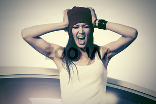 Angry fashion woman in tank top shouting beside a her car