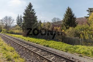 Schienen für Bahn im Gleis neben Garten im Frühling