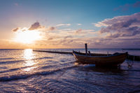Verträume Stimmung am Strand mit einem Boot aus Holz am Morgen