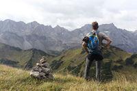 Wanderer macht Pause neben Steinmann