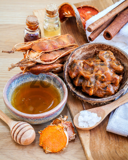 Homemade skin care and body scrub with natural ingredients tamarind, honey, himalayan salt ,turmeric and cinnamon set up on wooden background.