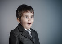 little businessman, brown-haired boy dressed in suit and tie with faces and funny expressions