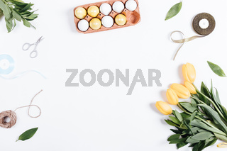 Painted eggs, tulips, rope, ribbon, scissors and place for text on a white background