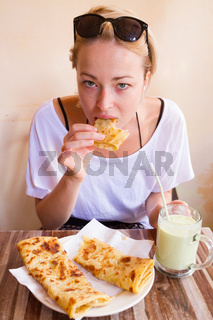 Woman eating traditional moroccan breakfast in coffee shop.