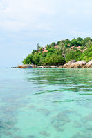 Heavenly green tropical island with clear sea and corals