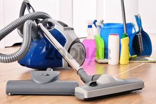 Vacuum cleaner and variety of detergent bottles and chemical cleaning supplies on the floor