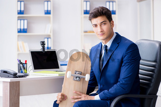 Young businessman with skate in office in sports concept