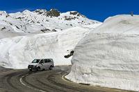 PKW fährt auf der Passtrasse zwischen hohen Schneemauern über den Gotthardpass, Schweiz