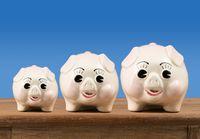 Small medium and large piggy banks on shelf