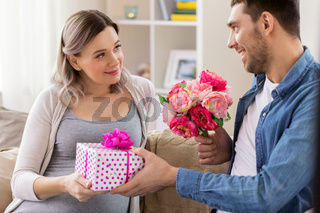 man giving flowers to pregnant woman at home