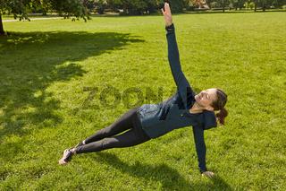 Frau macht Yoga im Park als Fitness Training