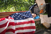 Homeless man using USA flag as a blanket.