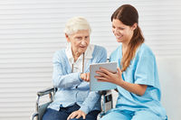 Neugierige Seniorin im Rollstuhl mit Tablet PC