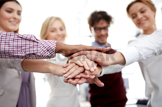 happy business team with hands on top at office