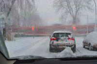 Ein PKW steht im Schneegestöber vor geschlossenen Bahnschranken