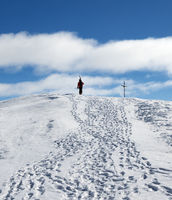 Skier with skis on his shoulder go up to top of snowy mountain