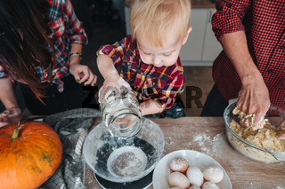 Little son helps in the kitchen to dad and mom