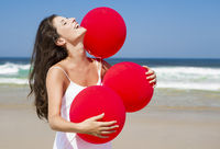 Beautiful girl holding red ballons