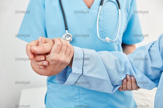 Hände von Pflegekraft stützen Hand von Patient