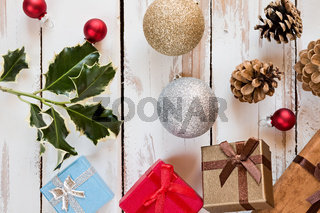 Closeup of Christmas presents and decorations over a rustic wooden table