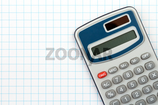 Digital calculator on squared paper background