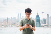 young man with mobile phone near water in modern city