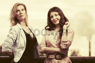 Two happy young fashion women walking in city street
