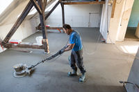 Laborer polishing sand and cement screed floor.