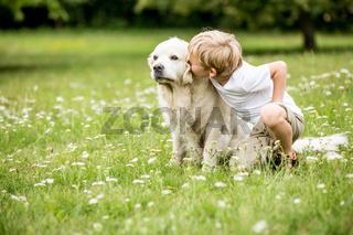 Kind küsst seinen Golden Retriever