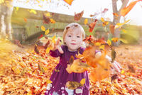 Little girl throwing fallen leaves