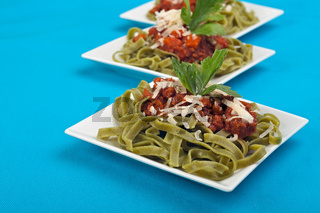 tagliatelle with sauce bolognaise in white plates