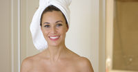 Smiling brunette wearing white towel on head