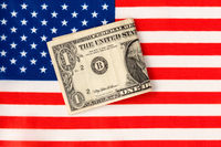 One Dollar bent in half and flag of the USA