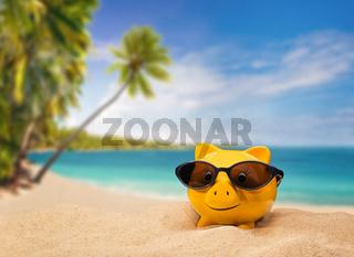 Glückliches Sparschwein auf einem tropischen Sandstrand