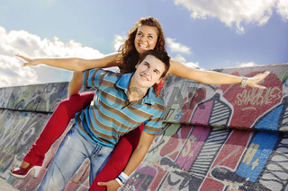 Young man giving piggyback to laughing woman