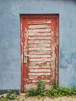 Rote Tür mit abblätternder Farbe in blauer Wand