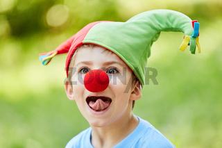 Junge mit Narrenkappe hat Spaß und zeigt Zunge