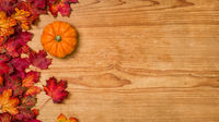 A wooden background with autumn foliage and a pumpkin