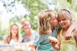 Junge küsst liebevoll seine Schwester