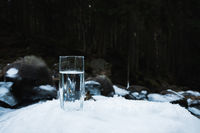 A transparent glass glass with drinking mountain water stands in the snow against a background of a forest in winter.