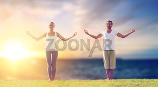 couple making yoga exercises outdoors