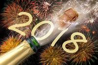 Knallende Champagnerflasche mit fliegendem Korken und Brillantfeuerwerk zu Silvester 2018