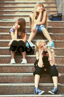 Group of happy fashion teen girls sitting on steps