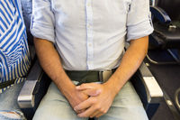 Male passenger with seat belt fastedned while sitting on airplane for safe flight.