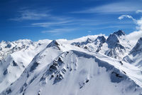 Winter mountains with snow cornice and blue sky with clouds