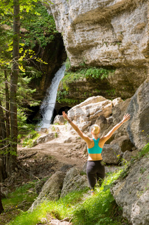Active woman raising arms inhaling fresh air, feeling relaxed in nature.