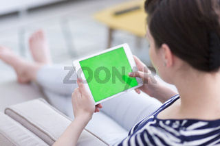 woman on sofa using tablet computer